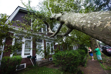 Cathy Alarie, right, and Jahyson Braxton, far right, look at Braxton's home in the 3200 block of North Third Street in Harrisburg after a tree was toppled onto the house by high winds from the Hurricane Irene storm system. PAUL CHAPLIN, The Patriot-News